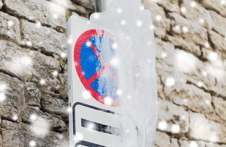 season, traffic and winter concept - iced no stopping road sign over wall