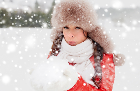 people, season and leisure concept - happy woman in winter fur hat blowing on snow in her hands outdoors Stock fotó