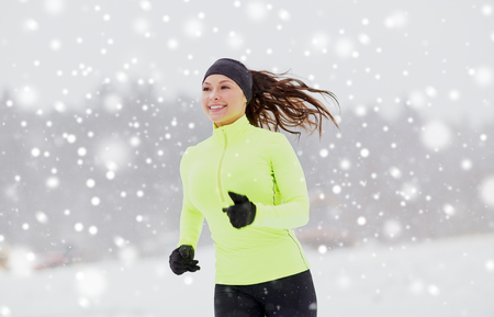 happy woman running along snow covered winter road