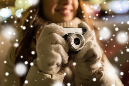 holidays, photography and people concept - close up of happy young woman with camera at christmas market in winter evening Stok Fotoğraf