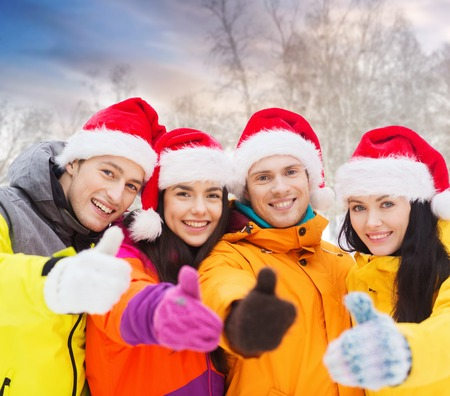 friends in santa hats showing thumbs up outdoors