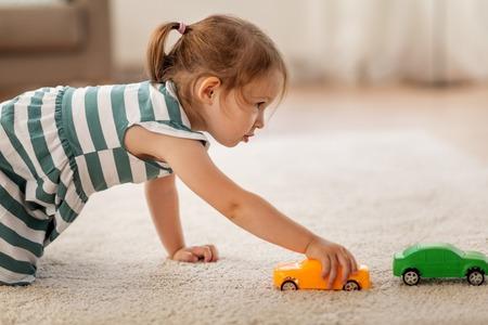 gelukkig babymeisje spelen met speelgoedauto thuis Stockfoto