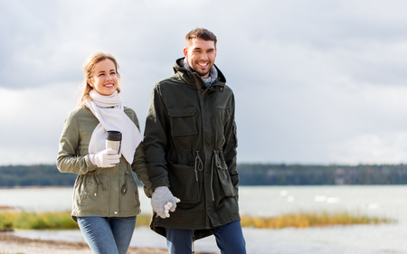 couple with tumbler walking along autumn beach