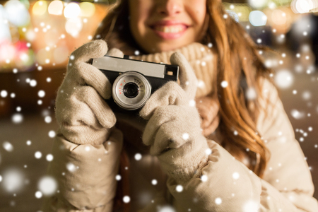 close up of happy woman with camera at christmas