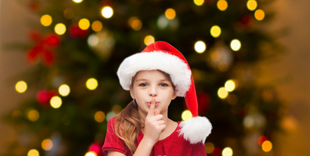 holidays and children concept - happy girl in santa hat making shh gesture over christmas tree lights background