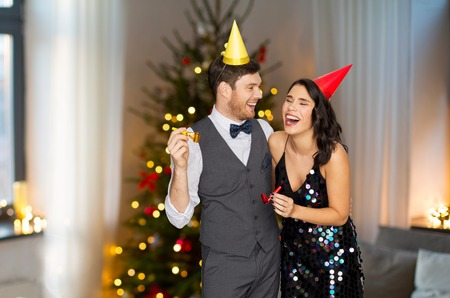 Couple with party blowers having fun on Christmas