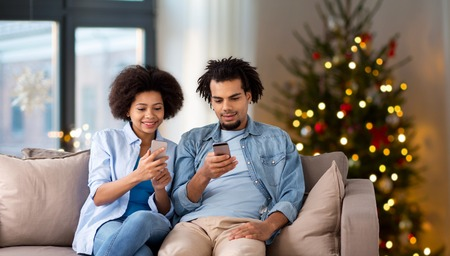 Happy couple with smartphones at home on Christmas