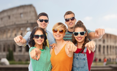 Friends in shades pointing at you over coliseum Stock Photo