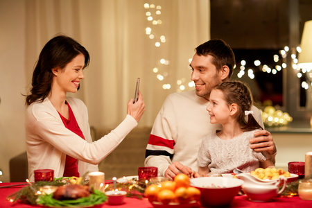 Happy family taking picture at Christmas dinner