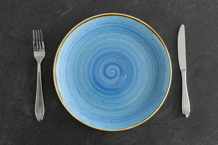 Close up of plate, fork and knife on table Banco de Imagens