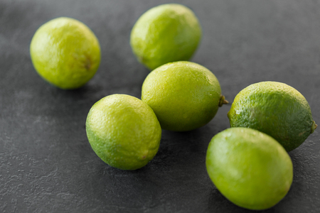 Close up of whole limes on slate table top