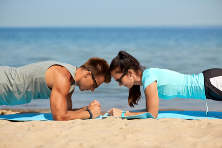 couple doing plank exercise on summer beach