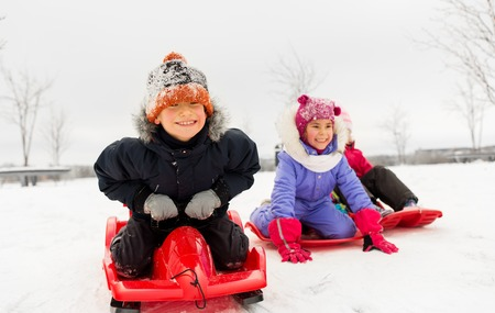 happy little kids sliding down on sleds in winter