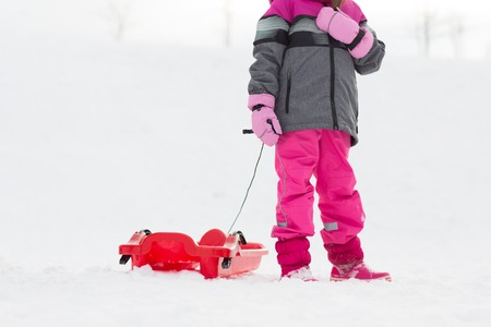 little girl with sled outdoors in winter