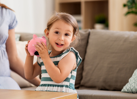 happy little girl with piggy bank