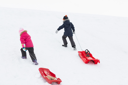 kids with sleds climbing snow hill in winter Banque d'images - 109567084