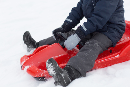childhood, sledging and season concept - close up of boy driving sled in winter