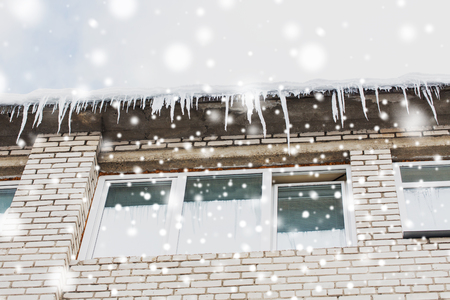 season, housing and winter concept - icicles on building or living house facade