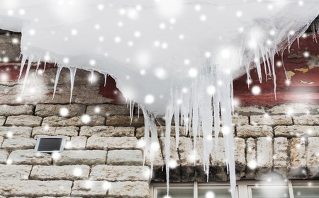 season, housing and winter concept - icicles and snow hanging from building roof Stock fotó