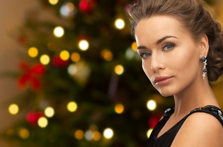 people, luxury, jewelry and fashion concept - close up of beautiful woman in black wearing diamond earring over christmas tree lights background Stock Photo