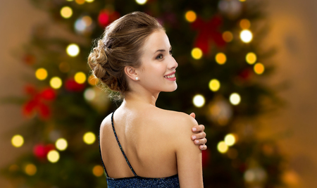 people, luxury and fashion concept - beautiful woman in festive dress over christmas tree lights background