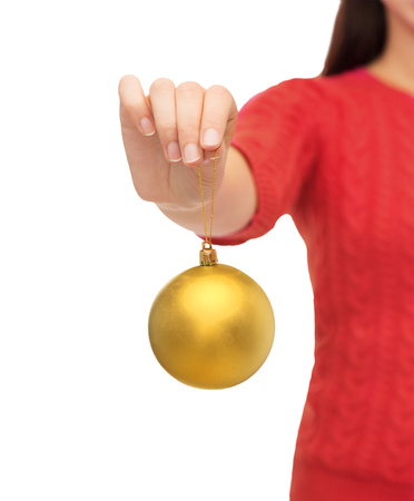 decoration, holidays and people concept - close up of woman hand holding christmas ball over white background
