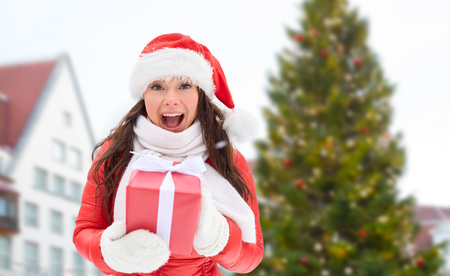 people, season and leisure concept - happy woman in santa hat with gift over christmas tree at tallinn old town hall square background