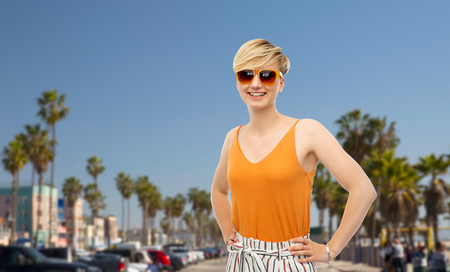 travel, tourism and summer holidays concept - happy smiling young woman in sunglasses over venice beach background in california Stock Photo