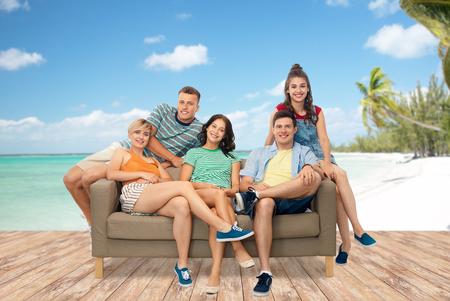 friends sitting on sofa over tropical beach