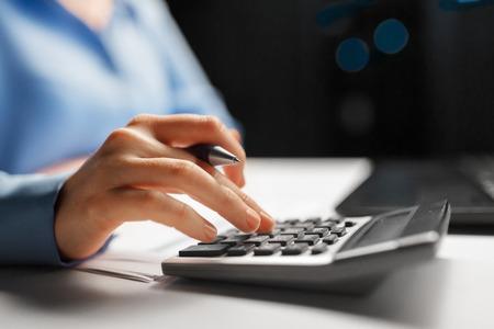 mujer de negocios, con, calculadora, en, noche, oficina