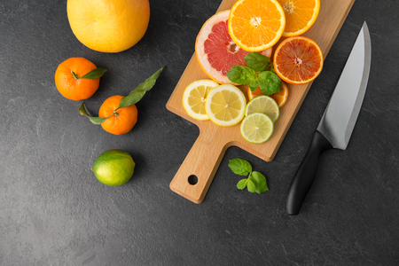 close up of fruits and knife on slate table top Stock Photo