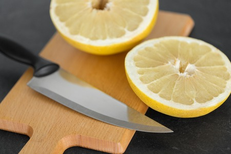close up of lemon and knife on cutting board Stock Photo