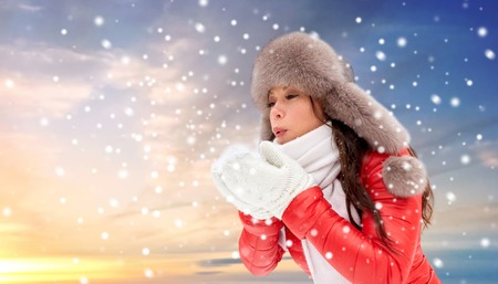 people, season and leisure concept - happy woman in winter fur hat blowing on snow in her hands outdoors over sky background and snow