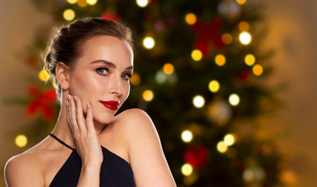 people, luxury and fashion concept - beautiful woman in black with red lips over christmas tree lights background