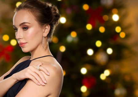 people, luxury, jewelry and fashion concept - beautiful woman in black wearing diamond earring and ring over christmas tree lights background Archivio Fotografico