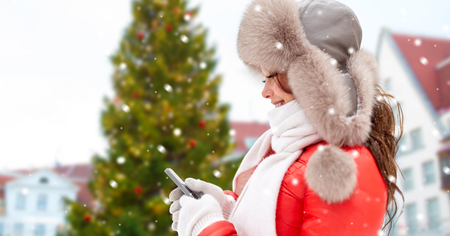 woman with smartphone over christmas tree Stock Photo