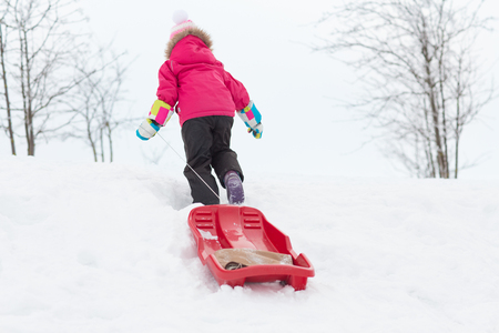 little girl with sleds on snow hill in winter Stok Fotoğraf