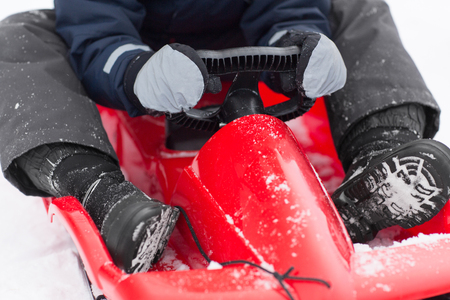 close up of boy driving sled in winter