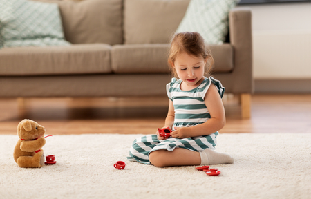 little girl playing with toy tea set at home Standard-Bild - 109920125