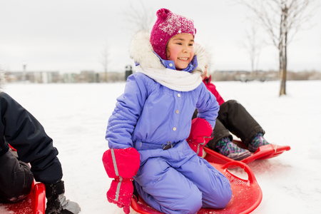 little girl on snow saucer sled in winter Standard-Bild - 109920127