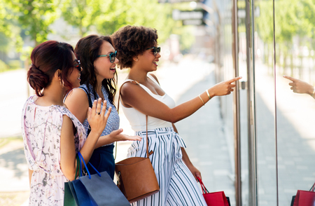 women with shopping bags looking at shop window Standard-Bild - 109920340