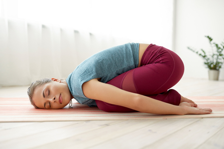 woman doing childs pose at yoga studio Standard-Bild - 109921253