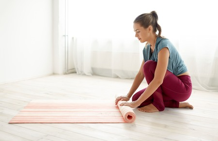 woman rolling up mat at yoga studio or gym Stock Photo