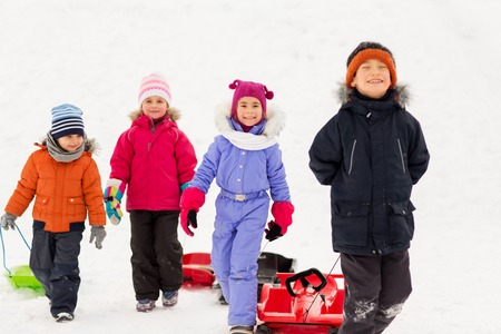 childhood, sledging and season concept - group of happy little kids with sleds in winter Standard-Bild - 109921758