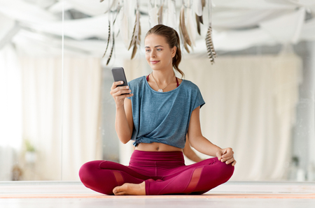 fitness, technology and healthy lifestyle concept - woman with smartphone at yoga studio Stock Photo