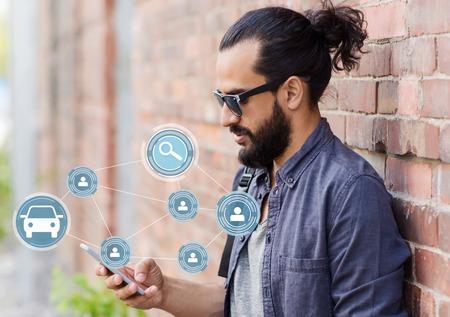 man die de app voor het delen van auto's op straat gebruikt Stockfoto