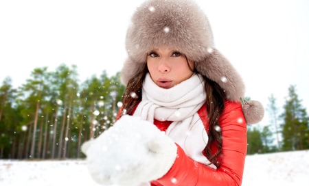 woman in fur hat with snow over winter forest