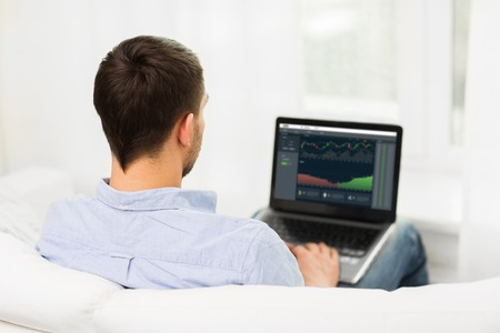 man with charts on laptop screen at home