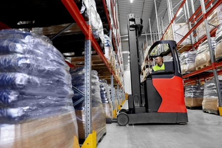 logistic business, shipment and loading concept - male loader operating forklift at warehouse Фото со стока