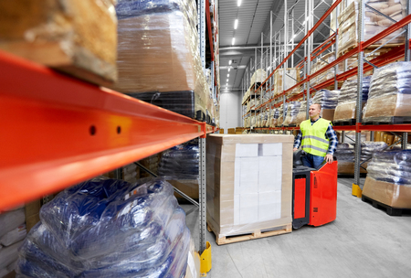 logistic business, shipment and loading concept - loader operating forklift with cargo at warehouse Фото со стока